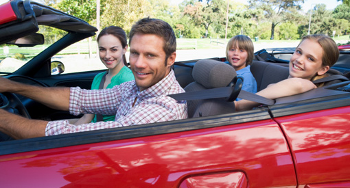 family riding in insured red sports car